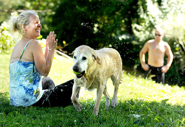 "Jill Lemaire, of Boulder, left, tries to dodge the wet tail of Daisy after playing fetch in the stream at Pineview Park on Friday, July 15, in Boulder. For a video of the park go to  <a href=""http://www.dailycamera.com"">http://www.dailycamera.com</a><br /> Jeremy Papasso/ Camera"
