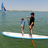 "Brennan Kane gets a paddle board ride from Roger Walker on Friday.<br /> Dozens of people cooled off in the Boulder reservoir on July 15, 2011. For more photos at the Rez, go to  <a href=""http://www.dailycamera.com"">http://www.dailycamera.com</a>.<br /> Cliff Grassmick / July 15, 2011"