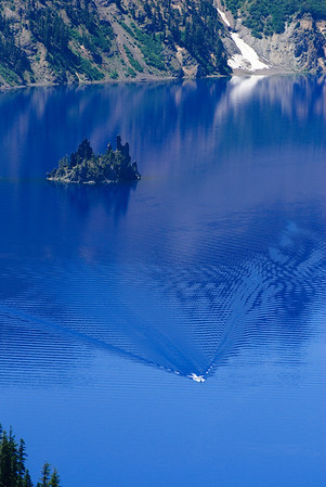 Phantom Ship Crater Lake, Oregon  note the tour boat in the lower part of the picture Post-processing note:  Pictures take with a circular polarizer.  Color and saturation were not adjusted.   It's really blue!