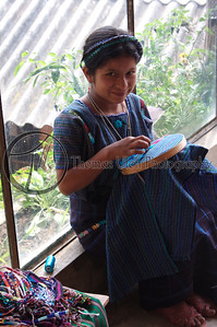 A young girl, hard at work in a shop in Santiago village on Lake Atitlan, Panajachel, Guatemala.