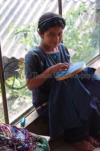 A young girl, hard at work in a shop in Santiago village on Lake Atitlan, Panajachel, Guatemala.