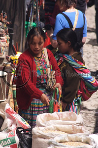 Buying the weekly corn. With a gringa tourist in the background shopping for a new purse. Women like to shop! Chichicastenango, Guatemala.