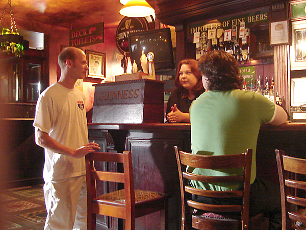 """Crew members in position for their roles as """"bartender"""" and """"customer"""" in the background, chatting with another crew member"""