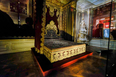 "The birthplace of Austria's longest-ruling emperor, Franz Josef, and bedroom of his parents Franz Karl and Sophie. On display here is the only surviving bed of state from the Viennese court. It was commissioned in 1723 for the imperial bedchamber of Maria Theresa's parents, Emperor Charles VI and Elizabeth Christine. As a ""bed of state"" it was not used in daily life. It was a ceremonial bed, used as a birthing place of, and place of baptism for, heirs to the imperial throne. In order to protect the rare textiles of the bed and walls, this room is exhibited behind glass. Of note in the corner of the room is the white porcelain and gilded stove. It was tended by servants from a passage behind the wall, out of view of those in the room. It provided heat during the cold Austian winters."