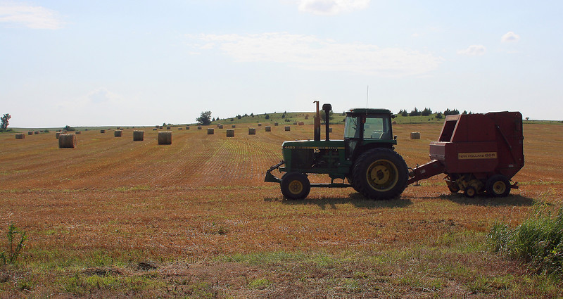 Tractor and rolled hay bales, Kansas.