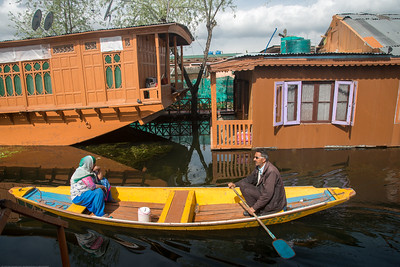 Shikaras ferry on Dal Lake between floating house boats. oDal Lake, Srinagar, Jammu and Kashmir, India.  They are usually moored at the edges of the Dal Lake and Nageen lakes. Some were built in the early 1900s, and are still being rented out to tourists.