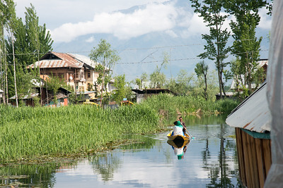 Residents use shikaras (boats) near the floating house boats on Dal Lake, Srinagar, Jammu and Kashmir, India.  House boats are usually moored at the edges of the Dal Lake and Nageen lakes. Some were built in the early 1900s, and are still being rented out to tourists.