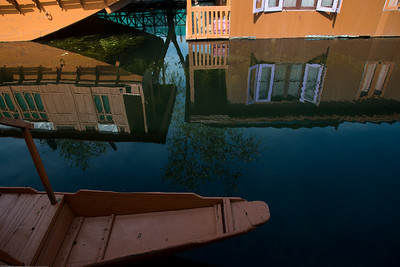Reflections in the Dal Lake.  Floating house boats on Dal Lake, Srinagar, Jammu and Kashmir, India. They are usually moored at the edges of the Dal Lake and Nageen lakes. Some were built in the early 1900s, and are still being rented out to tourists.