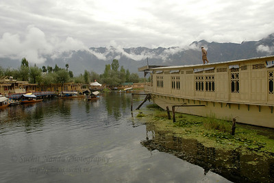 The house boat owner inspects the house boat roof which is floating in the Dal Lake, Srinagar, Kashmir, India. Also seen in the image are the small boats called shikaras.