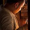 Buddhist man lighting candles.