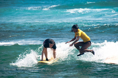 One woman surfer is trying to stand up, while another just flew off her surfboard , yet to hit the water.