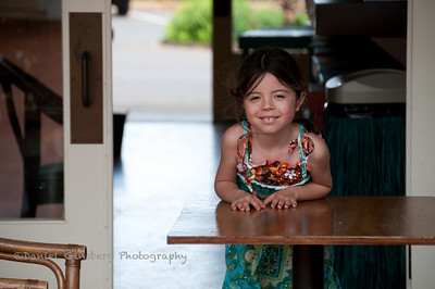 A little girl wearing a dress smiles at the camera while leaning over a table.