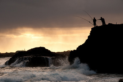 Fishing off rock above Glass Beach in 'Ele'ele in Kauai at sunset.