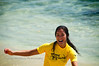 A pretty young woman, wearing a yellow Body Glove shirt, smiles after riding a wave on her surfboard.