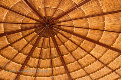 The bottom of a woven umbrella showing the spokes radiating out.