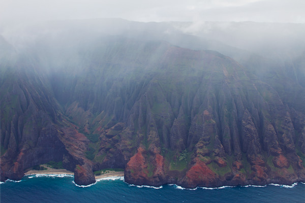 "The fabled Na Pali Coast was a bit obscured by clouds for our flight.  Note the two beaches with a rock between them.  There's an arch in that rock that someone once flew a plane through. After that the FAA said, ""No more""."