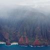 """The fabled Na Pali Coast was a bit obscured by clouds for our flight.  Note the two beaches with a rock between them.  There's an arch in that rock that someone once flew a plane through. After that the FAA said, """"No more""""."""