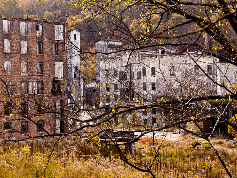 The Old Crow distillery has been closed for decades.  After a long decline it was bought by the Jim Beam corporation which used what barrel warehouses it could and left the rest to rot. A barrel warehouse can be seen on the left while the main distillery is on the right.  Had to prop the camera on a fence above  my head for this shot.