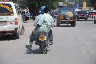Getting around in Musoma.  You hire the bike captain and he takes you wherever you want to go, an open air taxi.  Note that the rider gets the crash helmet and the passenger takes their chances.  Ladies ride sidesaddle.