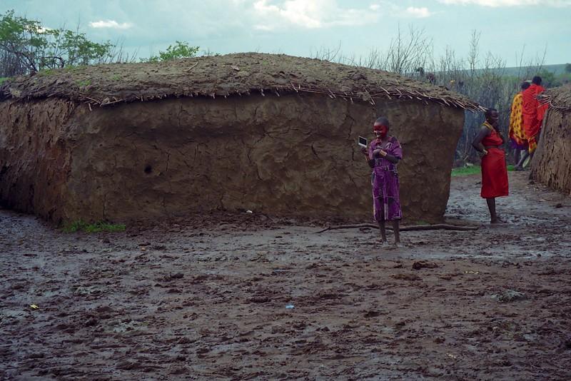 Massai girl looking at Polaroid of herself - Masai Mara, Kenya, March 1999
