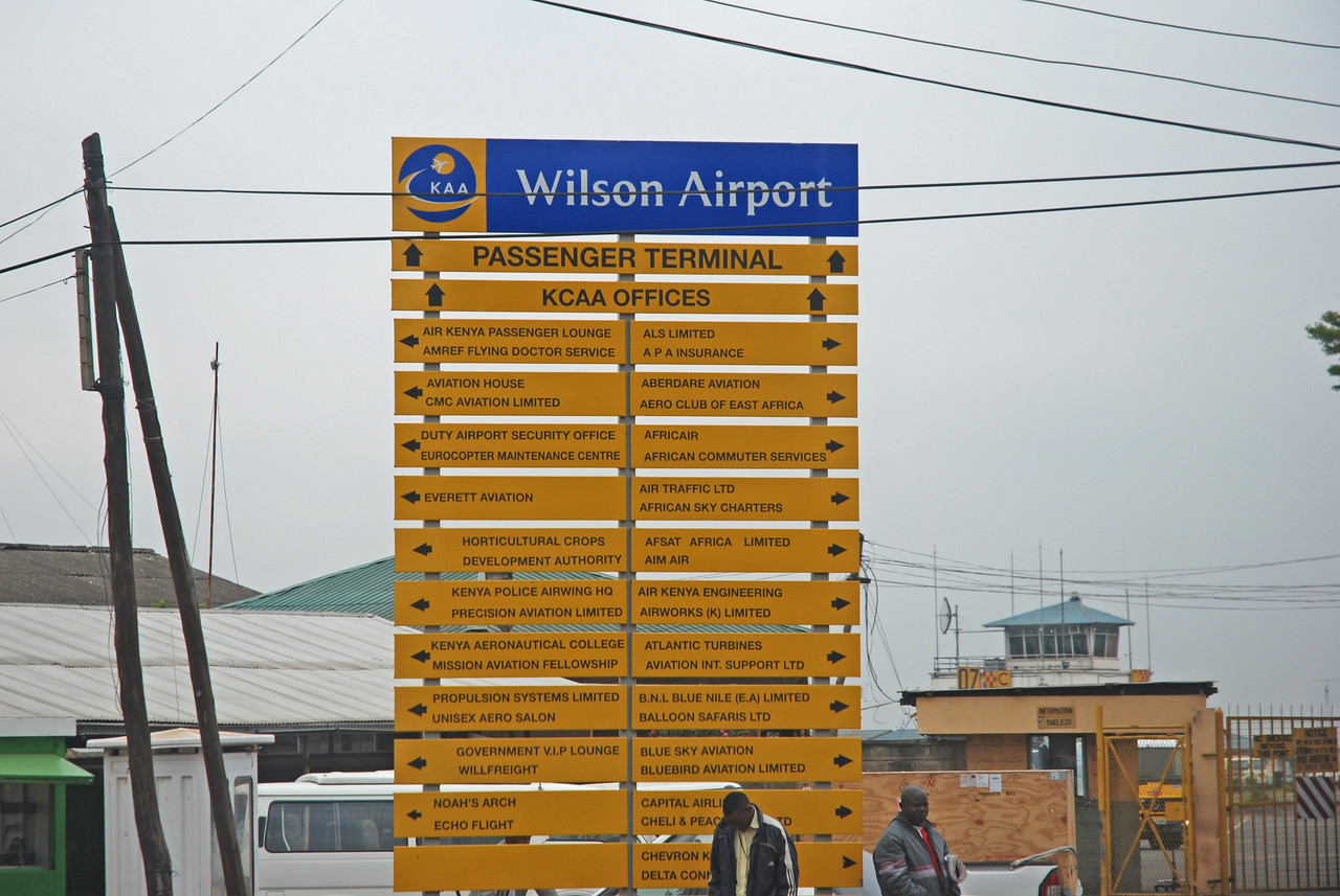 ← Wilson Airport, Nairobi <br /> <br /> We arrived at Wilson Airport to discover many burly policemen carrying alarming weapons and workers who were busily trimming bushes and sweeping the roads and pathways. The airport grounds at least were well-maintained and pristine. The airport building itself, however, looked a little on the far side of prime. To our surprise, it was a beehive of activity.