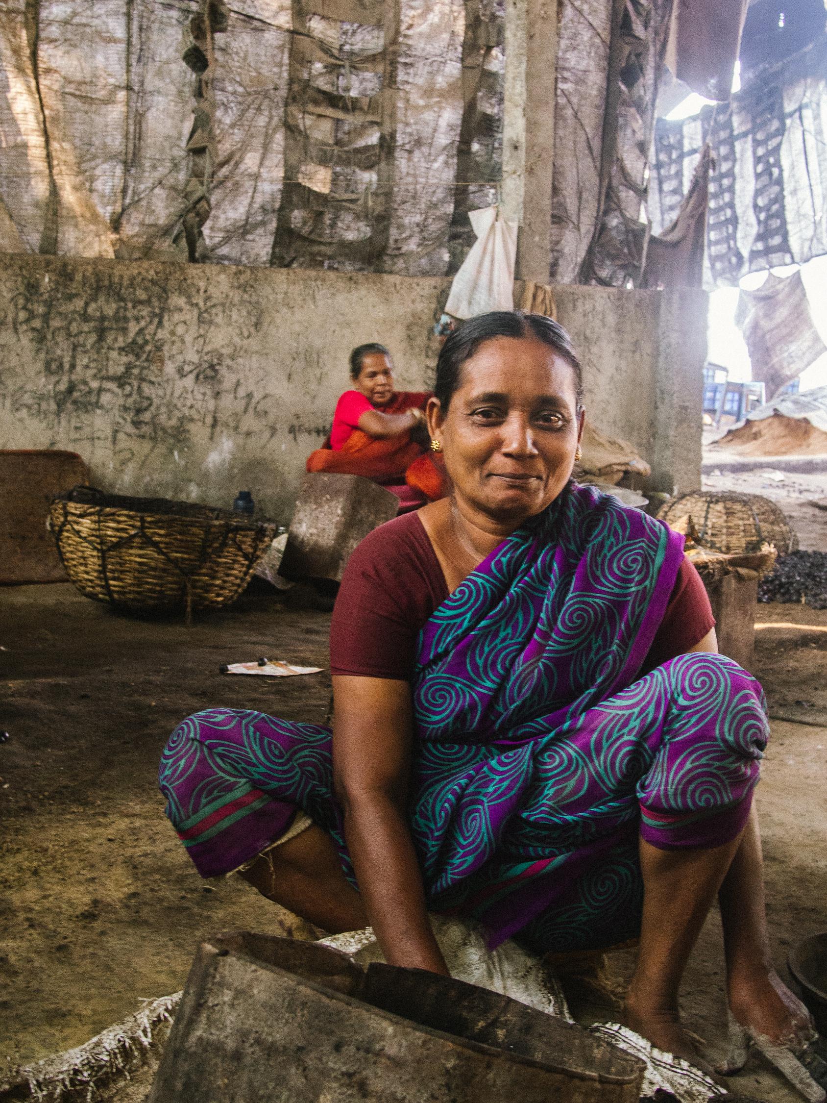 Woman smiling at camera in Kerala cashew factory
