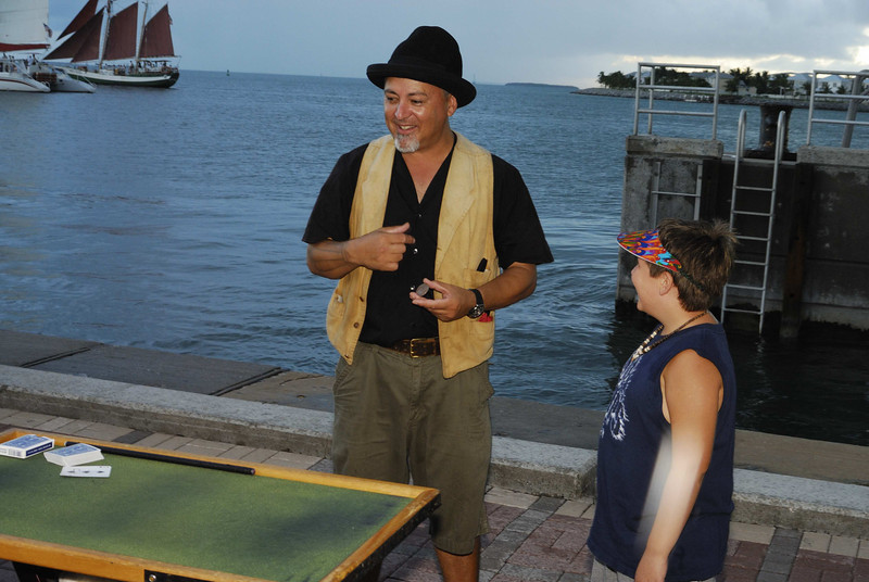 A magician at Mallory Square with an assistant from the audience.