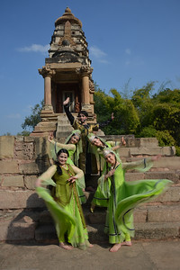 "Two Uzbek-dancers from Uzbekistan strike a pose at the Khajuraho Temple.  Khajuraho - Land Of The Moon God is located in the Indian state of Madhya Pradesh (MP) and roughly 620 kilometers (385 miles) southeast of New Delhi. Khajuraho was the cultural capital of the Chandela Rajputs, a Hindu dynasty that ruled from the 10th to 12th centuries. The temples of Khajuraho are famous for their so-called ""erotic sculptures"".  Symbolising a medieval legacy, the Khajuraho temples are a perfect fusion of architectural and sculptural excellence, representing one of the finest examples of Indian art. To some, they are the most graphic, erotic and sensuous sculptures the world has ever known. But Khajuraho has not received the attention it deserves for its significant contribution to the religious art of India - there are literally hundreds of exquisite images on the interior and exterior walls of the shrines.  Architecturally they are unique. While each temple has a distinct plan and design, several features are common to all. They are all built on high platforms, several metres off the ground. The stone used throughout is either granite or a combination of light sandstone and granite. Each of these temples has an entrance hall or mandapa, and a sanctum sanctorum or garbha griha. The roofs of these various sections have a distinct form. The porch and hall have pyramidal roofs made of several horizontal layers. The inner sanctum's roof is a conical tower - a colossal pile of stone (often 30m high) made of an arrangement of miniature towers called shikharas."