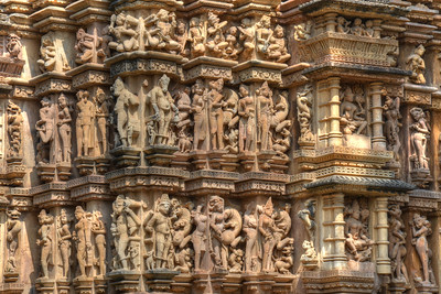 "Detailed carvings on the temple walls. Khajuraho - Land Of The Moon God is located in the Indian state of Madhya Pradesh (MP) and roughly 620 kilometers (385 miles) southeast of New Delhi. Khajuraho was the cultural capital of the Chandela Rajputs, a Hindu dynasty that ruled from the 10th to 12th centuries. The temples of Khajuraho are famous for their so-called ""erotic sculptures"".  Symbolising a medieval legacy, the Khajuraho temples are a perfect fusion of architectural and sculptural excellence, representing one of the finest examples of Indian art. To some, they are the most graphic, erotic and sensuous sculptures the world has ever known. But Khajuraho has not received the attention it deserves for its significant contribution to the religious art of India - there are literally hundreds of exquisite images on the interior and exterior walls of the shrines.  Architecturally they are unique. While each temple has a distinct plan and design, several features are common to all. They are all built on high platforms, several metres off the ground. The stone used throughout is either granite or a combination of light sandstone and granite. Each of these temples has an entrance hall or mandapa, and a sanctum sanctorum or garbha griha. The roofs of these various sections have a distinct form. The porch and hall have pyramidal roofs made of several horizontal layers. The inner sanctum's roof is a conical tower - a colossal pile of stone (often 30m high) made of an arrangement of miniature towers called shikharas."
