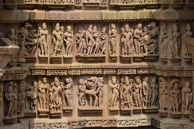 """Stone carvings at Khajuraho. Khajuraho - Land Of The Moon God is located in the Indian state of Madhya Pradesh (MP) and roughly 620 kilometers (385 miles) southeast of New Delhi. Khajuraho was the cultural capital of the Chandela Rajputs, a Hindu dynasty that ruled from the 10th to 12th centuries. The temples of Khajuraho are famous for their so-called """"erotic sculptures"""".  Symbolising a medieval legacy, the Khajuraho temples are a perfect fusion of architectural and sculptural excellence, representing one of the finest examples of Indian art. To some, they are the most graphic, erotic and sensuous sculptures the world has ever known. But Khajuraho has not received the attention it deserves for its significant contribution to the religious art of India - there are literally hundreds of exquisite images on the interior and exterior walls of the shrines.  Architecturally they are unique. While each temple has a distinct plan and design, several features are common to all. They are all built on high platforms, several metres off the ground. The stone used throughout is either granite or a combination of light sandstone and granite. Each of these temples has an entrance hall or mandapa, and a sanctum sanctorum or garbha griha. The roofs of these various sections have a distinct form. The porch and hall have pyramidal roofs made of several horizontal layers. The inner sanctum's roof is a conical tower - a colossal pile of stone (often 30m high) made of an arrangement of miniature towers called shikharas."""