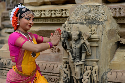 "Kuchipudi dancer Abhinaya Nagajothy at the Khajuraho Temple.  Khajuraho - Land Of The Moon God is located in the Indian state of Madhya Pradesh (MP) and roughly 620 kilometers (385 miles) southeast of New Delhi. Khajuraho was the cultural capital of the Chandela Rajputs, a Hindu dynasty that ruled from the 10th to 12th centuries. The temples of Khajuraho are famous for their so-called ""erotic sculptures"".  Symbolising a medieval legacy, the Khajuraho temples are a perfect fusion of architectural and sculptural excellence, representing one of the finest examples of Indian art. To some, they are the most graphic, erotic and sensuous sculptures the world has ever known. But Khajuraho has not received the attention it deserves for its significant contribution to the religious art of India - there are literally hundreds of exquisite images on the interior and exterior walls of the shrines.  Architecturally they are unique. While each temple has a distinct plan and design, several features are common to all. They are all built on high platforms, several metres off the ground. The stone used throughout is either granite or a combination of light sandstone and granite. Each of these temples has an entrance hall or mandapa, and a sanctum sanctorum or garbha griha. The roofs of these various sections have a distinct form. The porch and hall have pyramidal roofs made of several horizontal layers. The inner sanctum's roof is a conical tower - a colossal pile of stone (often 30m high) made of an arrangement of miniature towers called shikharas."