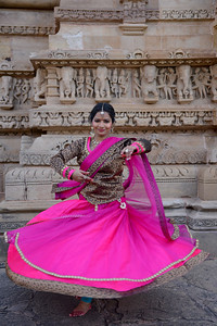 "Kathak dancer Smt Samiksha Sharma at the Khajuraho Temple.  Khajuraho - Land Of The Moon God is located in the Indian state of Madhya Pradesh (MP) and roughly 620 kilometers (385 miles) southeast of New Delhi. Khajuraho was the cultural capital of the Chandela Rajputs, a Hindu dynasty that ruled from the 10th to 12th centuries. The temples of Khajuraho are famous for their so-called ""erotic sculptures"".  Symbolising a medieval legacy, the Khajuraho temples are a perfect fusion of architectural and sculptural excellence, representing one of the finest examples of Indian art. To some, they are the most graphic, erotic and sensuous sculptures the world has ever known. But Khajuraho has not received the attention it deserves for its significant contribution to the religious art of India - there are literally hundreds of exquisite images on the interior and exterior walls of the shrines.  Architecturally they are unique. While each temple has a distinct plan and design, several features are common to all. They are all built on high platforms, several metres off the ground. The stone used throughout is either granite or a combination of light sandstone and granite. Each of these temples has an entrance hall or mandapa, and a sanctum sanctorum or garbha griha. The roofs of these various sections have a distinct form. The porch and hall have pyramidal roofs made of several horizontal layers. The inner sanctum's roof is a conical tower - a colossal pile of stone (often 30m high) made of an arrangement of miniature towers called shikharas."