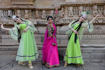"""Kathak & Uzbek dancers at the Khajuraho Temple.  Khajuraho - Land Of The Moon God is located in the Indian state of Madhya Pradesh (MP) and roughly 620 kilometers (385 miles) southeast of New Delhi. Khajuraho was the cultural capital of the Chandela Rajputs, a Hindu dynasty that ruled from the 10th to 12th centuries. The temples of Khajuraho are famous for their so-called """"erotic sculptures"""".  Symbolising a medieval legacy, the Khajuraho temples are a perfect fusion of architectural and sculptural excellence, representing one of the finest examples of Indian art. To some, they are the most graphic, erotic and sensuous sculptures the world has ever known. But Khajuraho has not received the attention it deserves for its significant contribution to the religious art of India - there are literally hundreds of exquisite images on the interior and exterior walls of the shrines.  Architecturally they are unique. While each temple has a distinct plan and design, several features are common to all. They are all built on high platforms, several metres off the ground. The stone used throughout is either granite or a combination of light sandstone and granite. Each of these temples has an entrance hall or mandapa, and a sanctum sanctorum or garbha griha. The roofs of these various sections have a distinct form. The porch and hall have pyramidal roofs made of several horizontal layers. The inner sanctum's roof is a conical tower - a colossal pile of stone (often 30m high) made of an arrangement of miniature towers called shikharas."""