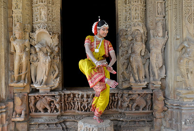 "Odissi dancer Bithika Mistry at the Khajuraho Temple.   Khajuraho - Land Of The Moon God is located in the Indian state of Madhya Pradesh (MP) and roughly 620 kilometers (385 miles) southeast of New Delhi. Khajuraho was the cultural capital of the Chandela Rajputs, a Hindu dynasty that ruled from the 10th to 12th centuries. The temples of Khajuraho are famous for their so-called ""erotic sculptures"".  Symbolising a medieval legacy, the Khajuraho temples are a perfect fusion of architectural and sculptural excellence, representing one of the finest examples of Indian art. To some, they are the most graphic, erotic and sensuous sculptures the world has ever known. But Khajuraho has not received the attention it deserves for its significant contribution to the religious art of India - there are literally hundreds of exquisite images on the interior and exterior walls of the shrines.  Architecturally they are unique. While each temple has a distinct plan and design, several features are common to all. They are all built on high platforms, several metres off the ground. The stone used throughout is either granite or a combination of light sandstone and granite. Each of these temples has an entrance hall or mandapa, and a sanctum sanctorum or garbha griha. The roofs of these various sections have a distinct form. The porch and hall have pyramidal roofs made of several horizontal layers. The inner sanctum's roof is a conical tower - a colossal pile of stone (often 30m high) made of an arrangement of miniature towers called shikharas."