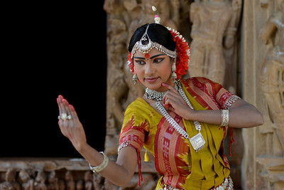 "Odissi dancer Bithika Mistry at the Khajuraho Temple strikes a dance pose.  Khajuraho - Land Of The Moon God is located in the Indian state of Madhya Pradesh (MP) and roughly 620 kilometers (385 miles) southeast of New Delhi. Khajuraho was the cultural capital of the Chandela Rajputs, a Hindu dynasty that ruled from the 10th to 12th centuries. The temples of Khajuraho are famous for their so-called ""erotic sculptures"".  Symbolising a medieval legacy, the Khajuraho temples are a perfect fusion of architectural and sculptural excellence, representing one of the finest examples of Indian art. To some, they are the most graphic, erotic and sensuous sculptures the world has ever known. But Khajuraho has not received the attention it deserves for its significant contribution to the religious art of India - there are literally hundreds of exquisite images on the interior and exterior walls of the shrines.  Architecturally they are unique. While each temple has a distinct plan and design, several features are common to all. They are all built on high platforms, several metres off the ground. The stone used throughout is either granite or a combination of light sandstone and granite. Each of these temples has an entrance hall or mandapa, and a sanctum sanctorum or garbha griha. The roofs of these various sections have a distinct form. The porch and hall have pyramidal roofs made of several horizontal layers. The inner sanctum's roof is a conical tower - a colossal pile of stone (often 30m high) made of an arrangement of miniature towers called shikharas."