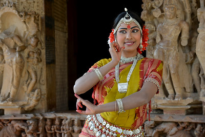 "Odissi dancer Bithika Mistry strikes a dance pose at the Khajuraho Temple.   Khajuraho - Land Of The Moon God is located in the Indian state of Madhya Pradesh (MP) and roughly 620 kilometers (385 miles) southeast of New Delhi. Khajuraho was the cultural capital of the Chandela Rajputs, a Hindu dynasty that ruled from the 10th to 12th centuries. The temples of Khajuraho are famous for their so-called ""erotic sculptures"".  Symbolising a medieval legacy, the Khajuraho temples are a perfect fusion of architectural and sculptural excellence, representing one of the finest examples of Indian art. To some, they are the most graphic, erotic and sensuous sculptures the world has ever known. But Khajuraho has not received the attention it deserves for its significant contribution to the religious art of India - there are literally hundreds of exquisite images on the interior and exterior walls of the shrines.  Architecturally they are unique. While each temple has a distinct plan and design, several features are common to all. They are all built on high platforms, several metres off the ground. The stone used throughout is either granite or a combination of light sandstone and granite. Each of these temples has an entrance hall or mandapa, and a sanctum sanctorum or garbha griha. The roofs of these various sections have a distinct form. The porch and hall have pyramidal roofs made of several horizontal layers. The inner sanctum's roof is a conical tower - a colossal pile of stone (often 30m high) made of an arrangement of miniature towers called shikharas."
