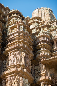 """Stone carved statues at Khajuraho Temple complex. Khajuraho - Land Of The Moon God is located in the Indian state of Madhya Pradesh (MP) and roughly 620 kilometers (385 miles) southeast of New Delhi. Khajuraho was the cultural capital of the Chandela Rajputs, a Hindu dynasty that ruled from the 10th to 12th centuries. The temples of Khajuraho are famous for their so-called """"erotic sculptures"""".   Symbolising a medieval legacy, the Khajuraho temples are a perfect fusion of architectural and sculptural excellence, representing one of the finest examples of Indian art. To some, they are the most graphic, erotic and sensuous sculptures the world has ever known. But Khajuraho has not received the attention it deserves for its significant contribution to the religious art of India - there are literally hundreds of exquisite images on the interior and exterior walls of the shrines."""