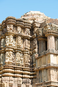 """The Khajuraho Duladeo Temple is a Hindu temple in Khajuraho, Madhya Pradesh, India. The temple is dedicated to the god Shiva in the form of a linga, which is deified in the sanctum. 'Dulodeo' means """"Holy Bridegroom"""". The temple is also known as """"Kunwar Math"""". It  is part of the Southern group of the Khajuraho group of temples.  Khajuraho Temples are all built on high platforms, several metres off the ground. The stone used throughout is either granite or a combination of light sandstone and granite. Each of these temples has an entrance hall or mandapa, and a sanctum sanctorum or garbha griha. The roofs of these various sections have a distinct form. The porch and hall have pyramidal roofs made of several horizontal layers. The inner sanctum's roof is a conical tower - a colossal pile of stone (often 30m high) made of an arrangement of miniature towers called shikharas."""
