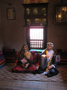 Omani couple in traditional dress (that's a flyswat they are each holding).