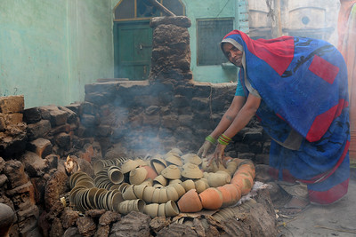 "Lady of the house lighting a fire for making clay works.  खुर्जा Khurja is a city in Bulandshahr district of Uttar Pradesh in north India. It is situated around 85 km from Delhi and is famous for its pottery. Khurja supplies a large portion of the ceramics and pottery used in the country and also exports the same. Hence Khurja is sometime called ""Khurja: The Ceramics City""  The history of Khurja Pottery goes back to about 600 years ago, when some of the potter's families moved to Khurja during reign of Emperor Mohammad-bin-Tughlak from Delhi and started with red clay Pottery. They moved on to blue glaze which became very popular. Clay articles with engobe of white clay, painting floral designs with cupric oxide and applying a soft glaze (containing glass and borax etc.) were the hall mark of this small city in UP."