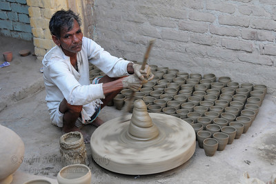 "Local single household potter family making kulads (clay drinking glasses).  खुर्जा Khurja is a city in Bulandshahr district of Uttar Pradesh in north India. It is situated around 85 km from Delhi and is famous for its pottery. Khurja supplies a large portion of the ceramics and pottery used in the country and also exports the same. Hence Khurja is sometime called ""Khurja: The Ceramics City""  The history of Khurja Pottery goes back to about 600 years ago, when some of the potter's families moved to Khurja during reign of Emperor Mohammad-bin-Tughlak from Delhi and started with red clay Pottery. They moved on to blue glaze which became very popular. Clay articles with engobe of white clay, painting floral designs with cupric oxide and applying a soft glaze (containing glass and borax etc.) were the hall mark of this small city in UP."