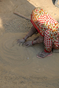 "Lady preparing soil for clay-pot-making in Khurja, UP.  खुर्जा Khurja is a city in Bulandshahr district of Uttar Pradesh in north India. It is situated around 85 km from Delhi and is famous for its pottery. Khurja supplies a large portion of the ceramics and pottery used in the country and also exports the same. Hence Khurja is sometime called ""Khurja: The Ceramics City""  The history of Khurja Pottery goes back to about 600 years ago, when some of the potter's families moved to Khurja during reign of Emperor Mohammad-bin-Tughlak from Delhi and started with red clay Pottery. They moved on to blue glaze which became very popular. Clay articles with engobe of white clay, painting floral designs with cupric oxide and applying a soft glaze (containing glass and borax etc.) were the hall mark of this small city in UP."