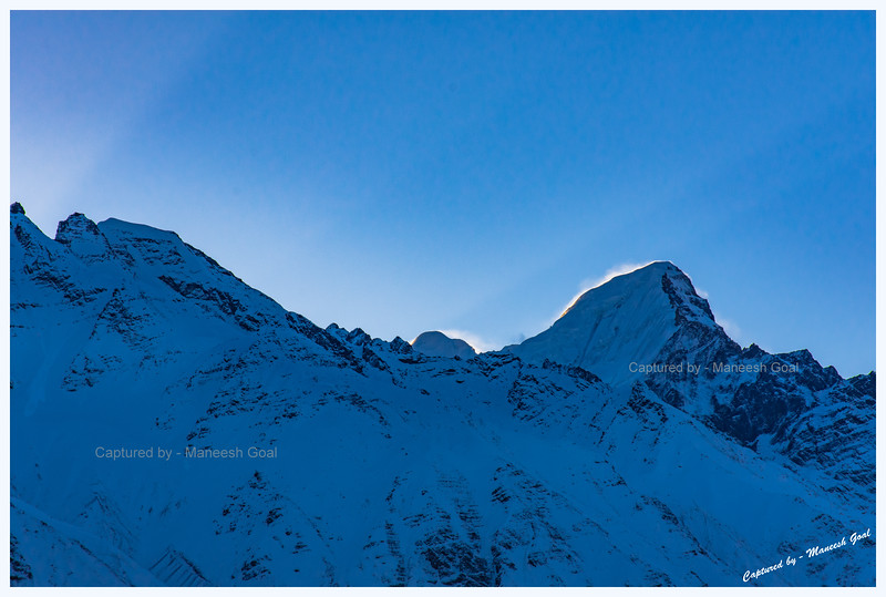 First rays of light hit the mountain peak. Chitkul