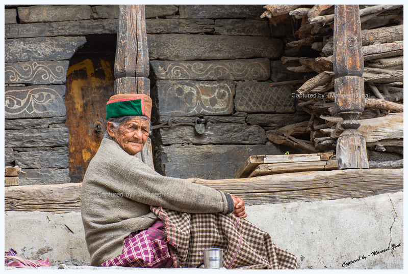 Old woman outside a heritage Himachali house, Kamru Village