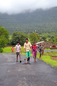 Playfull village children having fun with a self-made toy on the road near Kolwan, Maharashtra (MH), India.