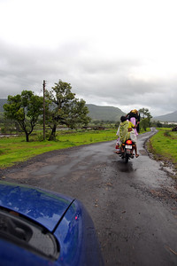 Multiple riders on a bike (motor cycle) on the road to Chinmaya Vibhooti, Kolwan, Maharashtra (MH), India