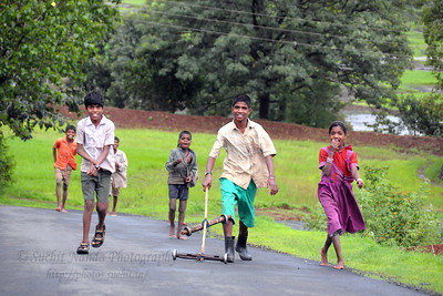Village children playing with a self-made toy on the road near Kolwan, Maharashtra (MH), India