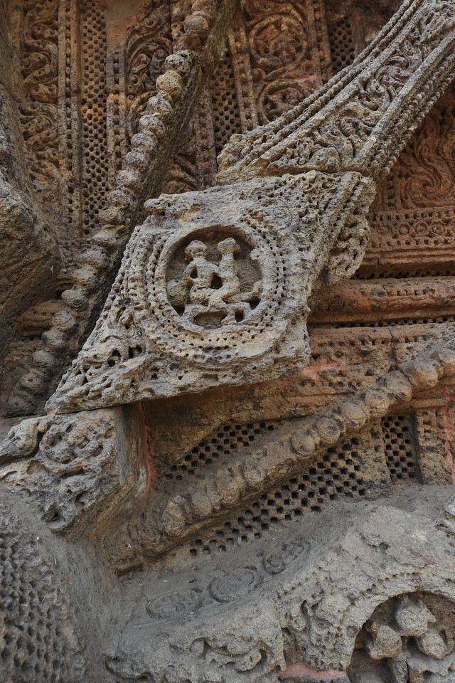 Close up view of the detailed work on the wheels of the Sun Temple, in Konark showing erotic art.<br /> <br /> Konark Sun Temple in Orissa belongs to the Kalinga school of Indian temples and was constructed by King Narasimhadeva of the Eastern Ganga Dynasty in the 13th Century. This world heritage site temple takes the form of a colossal chariot of Surya (Sun) drawn by seven spirited horses on twelve pairs of exquitely decorated wheels. Surya has been a popular deity in India since the Vedic perios. Thousands of sculptured images depict deities, celestial and human musicians, dancers, lovers, and myriad scenes of courtly life, ranging from hunts and military battles to the pleasures of courtly relaxation. The temple is famous for its erotic stone sculptures, which can be found primarily on the second level of the porch structure.