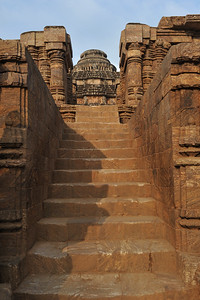 Konark Sun Temple in Orissa belongs to the Kalinga school of Indian temples and was constructed by King Narasimhadeva of the Eastern Ganga Dynasty in the 13th Century. This world heritage site temple takes the form of a colossal chariot of Surya (Sun) drawn by seven spirited horses on twelve pairs of exquitely decorated wheels. Surya has been a popular deity in India since the Vedic perios. Thousands of sculptured images depict deities, celestial and human musicians, dancers, lovers, and myriad scenes of courtly life, ranging from hunts and military battles to the pleasures of courtly relaxation. The temple is famous for its erotic stone sculptures, which can be found primarily on the second level of the porch structure.