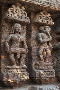 Musicians seen on the stone carvings of the wall of Konark Temple.  Konark Sun Temple in Orissa belongs to the Kalinga school of Indian temples and was constructed by King Narasimhadeva of the Eastern Ganga Dynasty in the 13th Century. This world heritage site temple takes the form of a colossal chariot of Surya (Sun) drawn by seven spirited horses on twelve pairs of exquitely decorated wheels. Surya has been a popular deity in India since the Vedic perios. Thousands of sculptured images depict deities, celestial and human musicians, dancers, lovers, and myriad scenes of courtly life, ranging from hunts and military battles to the pleasures of courtly relaxation. The temple is famous for its erotic stone sculptures, which can be found primarily on the second level of the porch structure. Orissa, India.
